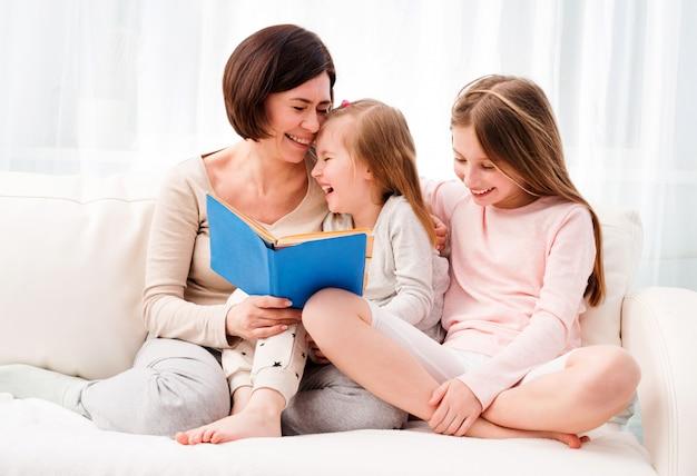 Mãe e filhas reaading livro infantil