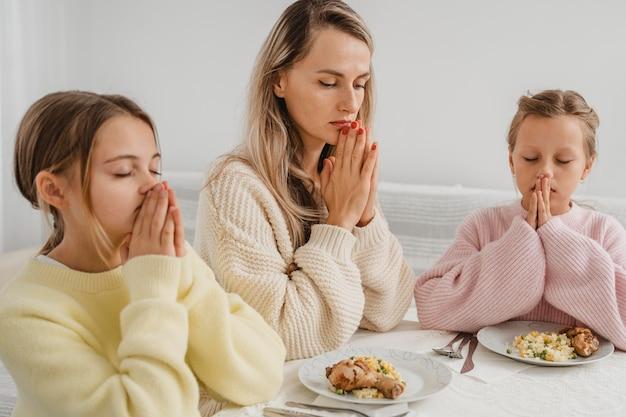 Mãe e filhas rezando à mesa de jantar