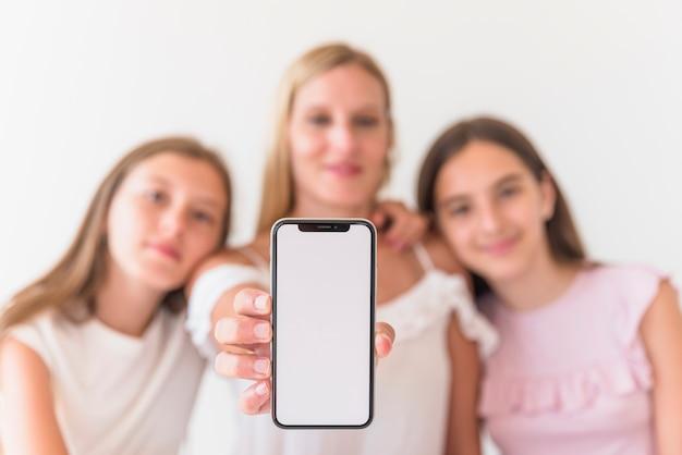 Mãe e filhas segurando smartphone com tela em branco