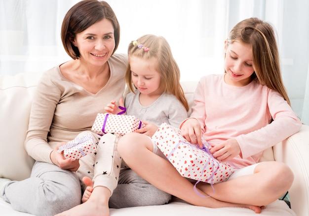 Mãe e filhas trocando presentes