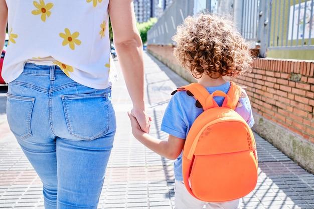 Mãe e filho a caminho da escola de mãos dadas