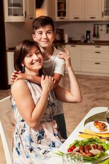 Mãe e filho abraçaram na mesa de jantar