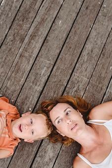 Mãe e filho adorável juntos deitado jogando e rindo em tábuas de madeira