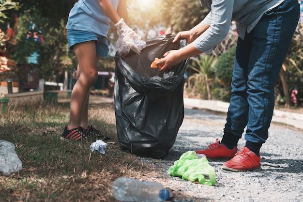 Mãe e filho ajudam a recolher o lixo no parque