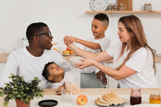 Mãe e filho, alimentando o pai com comida