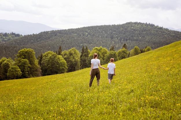 Mãe e filho andam de mãos dadas em um campo verde