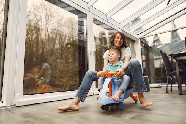 Mãe e filho andam pelo apartamento em um carro de brinquedo