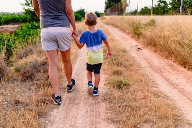 Mãe e filho andando de costas.