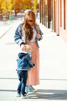 Mãe e filho andando na rua e família usando máscara facial ao ar livre.
