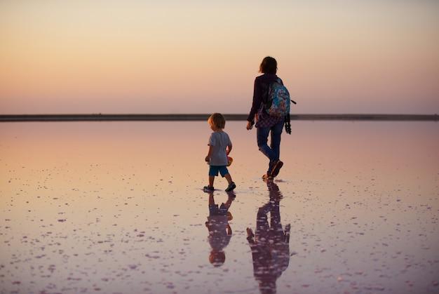 Mãe e filho andando sobre um sal e salmoura de um lago rosa, na
