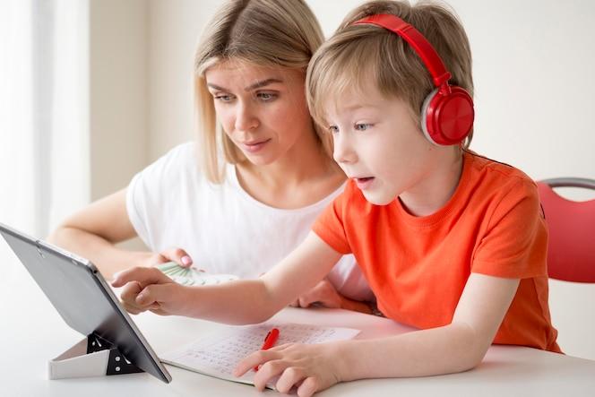 Mãe e filho aprendendo cursos sobre tablet digital