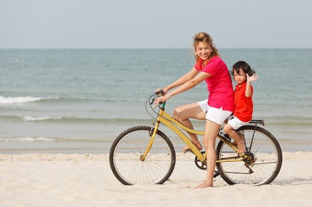 Mãe e filho asiáticos andando de bicicleta em praia tropical