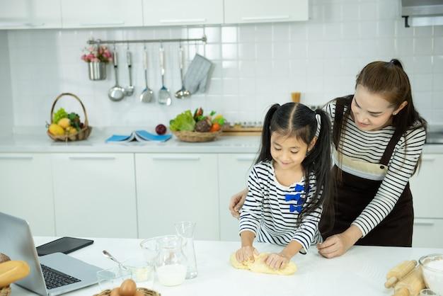 Mãe e filho asiáticos cozinham de farinha na cozinha, atividade de lazer em casa.