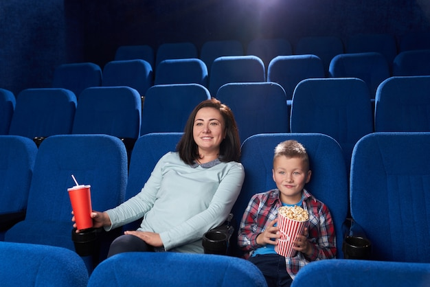 Mãe e filho assistindo filme no cinema.