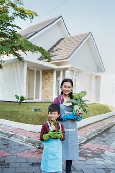 Mãe e filho atividade de jardinagem juntos no jardim de casa