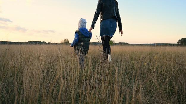 Mãe e filho atravessam o campo ao pôr do sol.