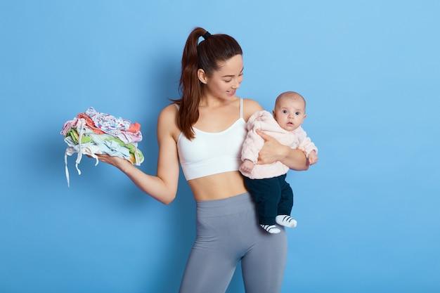 Mãe e filho bebê criança menina indoor, mamãe olhando para sua filha recém-nascida, segura roupas de crianças na outra mão, isoladas sobre fundo azul, mulher cativante com bebê vestindo roupas esportivas.