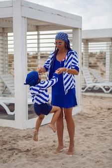 Mãe e filho bebê em jaquetas azuis listradas caminham pela praia ao lado de um mirante de madeira