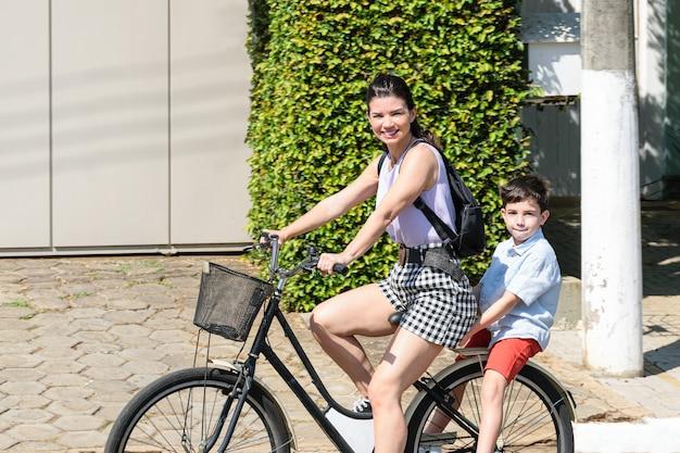 Mãe e filho brasileiros andando de bicicleta e olhando para a câmera.