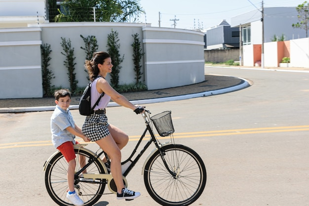 Mãe e filho brasileiros andando de bicicleta em uma manhã ensolarada.
