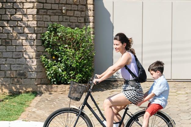 Mãe e filho brasileiros relaxando e andando de bicicleta em uma manhã ensolarada.