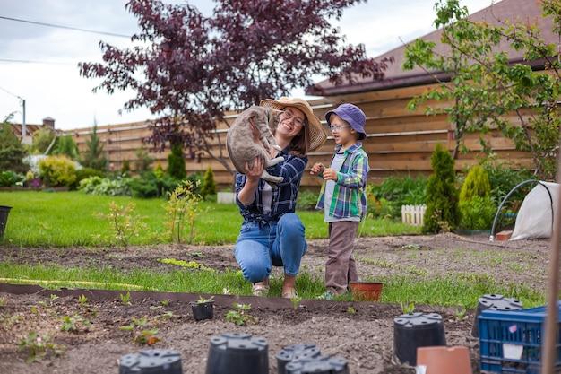 Mãe e filho brincam com gato doméstico no jardim do quintal
