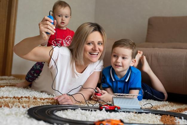 Mãe e filho brincam de corrida no tapete, e a filhinha senta-se nas costas da mãe.