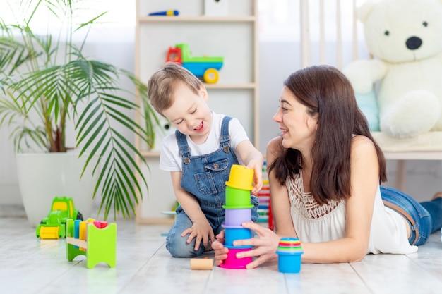 Mãe e filho brincam em casa com brinquedos educativos na sala das crianças. uma família feliz e amorosa.