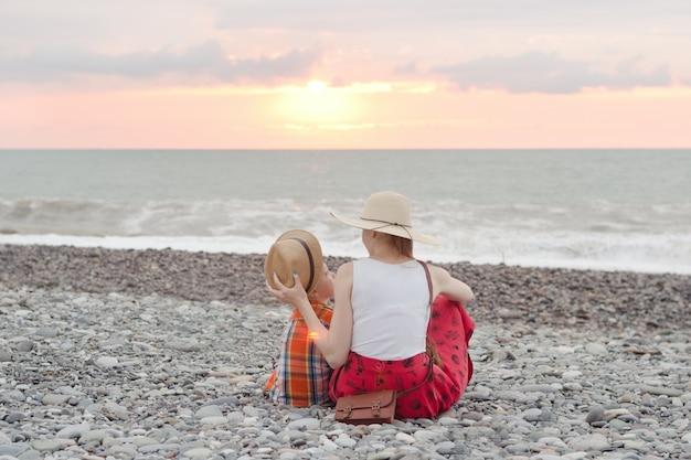 Mãe e filho brincam na praia de calhau.