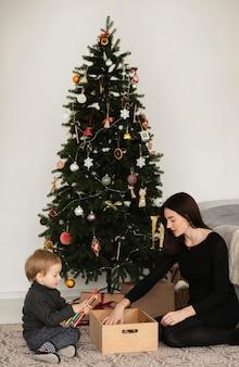 Mãe e filho brincando ao lado da árvore de natal