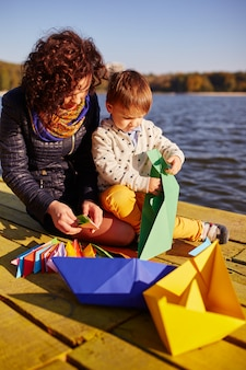 Mãe e filho brincando com barquinhos de papel à beira do lago