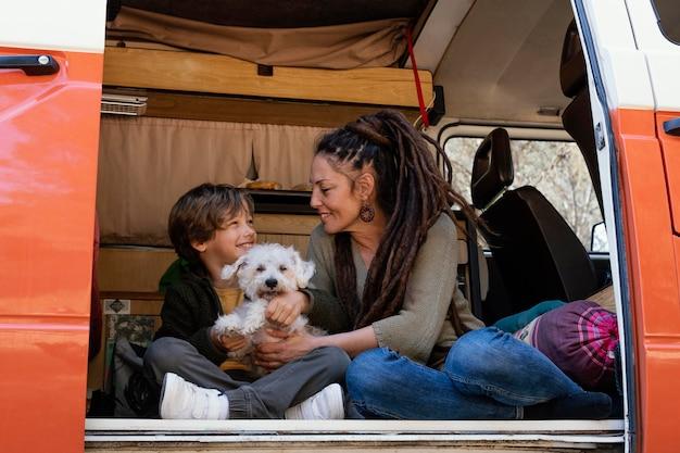Mãe e filho brincando com cachorro no carro