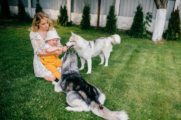 Mãe e filho brincando com dois cachorros no jardim