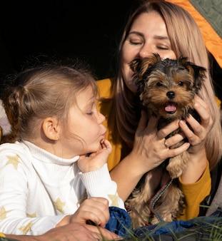 Mãe e filho brincando com o cachorro