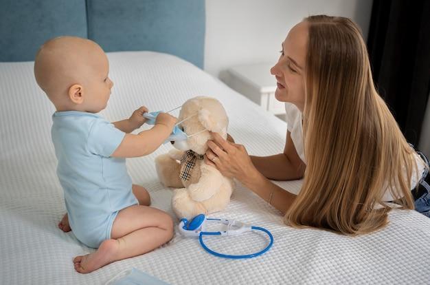 Mãe e filho brincando com o ursinho de pelúcia em casa