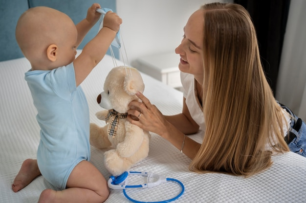 Mãe e filho brincando com o ursinho de pelúcia