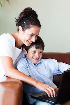 Mãe e filho brincando com um laptop