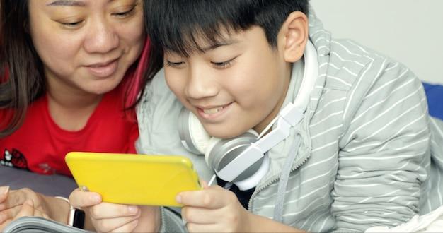 Mãe e filho brincando com um smartphone juntos.