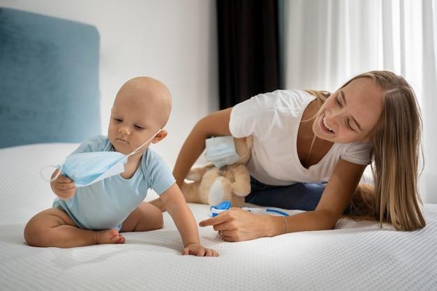 Mãe e filho brincando com um ursinho de pelúcia e uma máscara médica