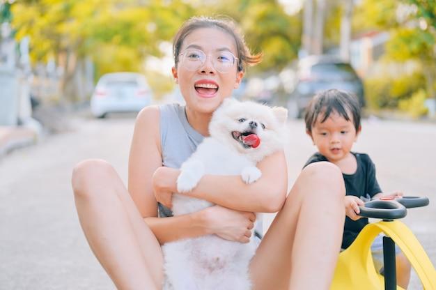 Mãe e filho brincando na estrada na hora do dia com o cachorrinho da pomerânia. conceito de família amigável. Foto Premium