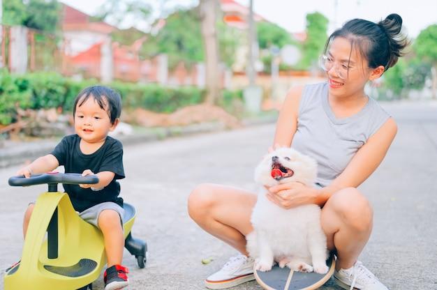 Mãe e filho brincando na estrada na hora do dia com o cachorrinho da pomerânia. conceito de família amigável.