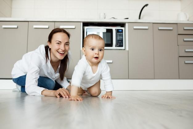 Mãe e filho brincando no chão da cozinha, se divertindo