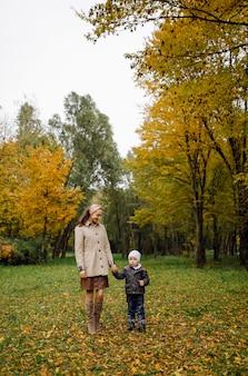 Mãe e filho caminhando e se divertindo juntos no parque outono.