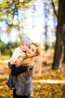 Mãe e filho caminhando em um parque de outono