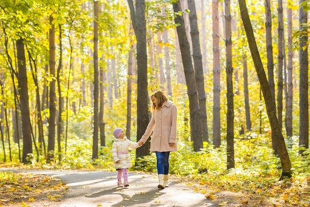 Mãe e filho caminhando no parque outono.