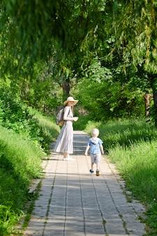 Mãe e filho caminhando pela estrada no parque. vista traseira. quadro vertical
