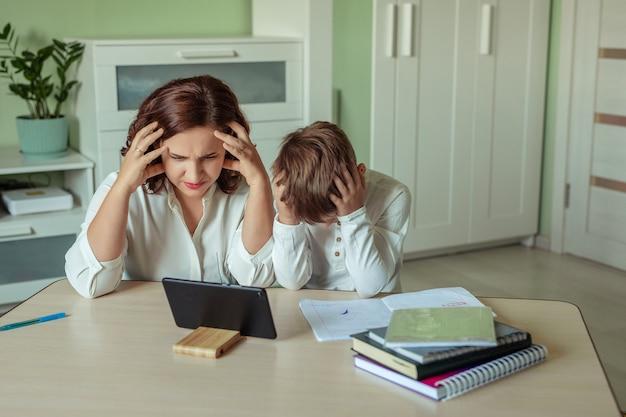 Mãe e filho cansados e chateados fazem a lição de casa usando um tablet.