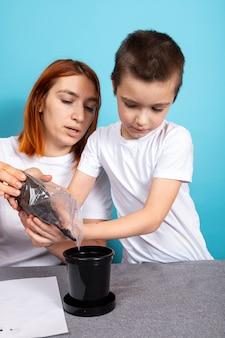 Mãe e filho colocam terra em um vaso preto para plantar uma semente e cultivar uma planta de casa em uma mesa contra uma superfície azul.