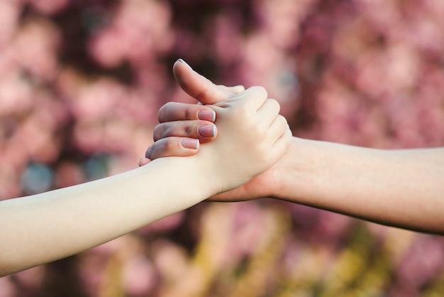 Mãe e filho com as mãos no fundo da natureza apoio familiar ajuda e confiança