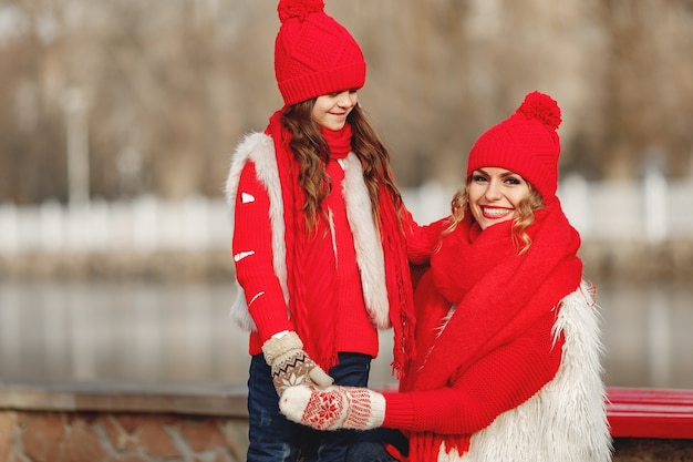 Mãe e filho com chapéus de malha de inverno nas férias de natal em família. chapéu de lã feito à mão e lenço para mãe e filho. tricô para crianças. casacos de malha. mulher e menina em um parque.